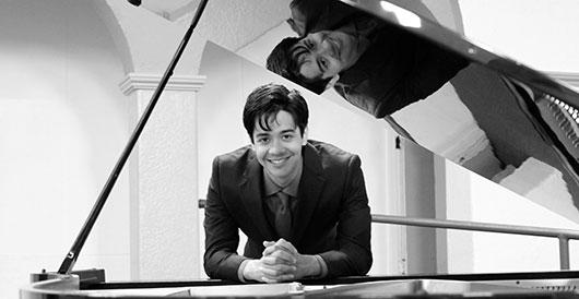 Josh Vigran posing with a piano.