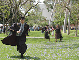 CSULB graduate running across the campus.