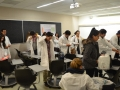students broaching lab coats